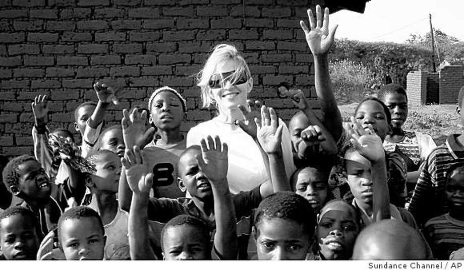 """In this image released by the Sundance Channel, pop star Madonna is surrounded by children in Malawi in a scene from her documentary, """"I Am Because We Are,"""" airing on the Sundance Channel on Monday, Dec. 1, 2008 at 9:00 p.m. EDT. (AP Photo/Sundance Channel) ** NO SALES ** Photo: Sundance Channel, AP"""
