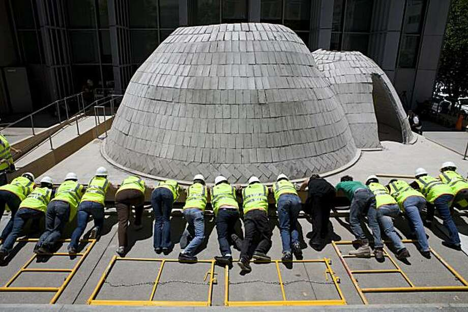 Volunteers push on the plywood foundation of the twin bowls at Yerba Buena Center (YBCA) for the Arts during the seismic test on Friday, July 2, 2010 in San Francisco. Photo: John Sebastian Russo, The Chronicle