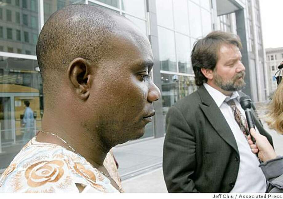 Larry Bowoto, left, of Bowoto v. Chevron, listens as attorney Bert Voorhees, right, speaks outside of the Federal Building in San Francisco, Monday, Dec. 1, 2008. A federal jury has cleared Chevron Corp. of responsibility for any human rights abuses during a violent protest on a company oil platform in Nigeria a decade ago. Human rights groups had sued the company under a centuries-old law allowing foreigners to file lawsuits in U.S. courts alleging international law violations. Photo: Jeff Chiu, Associated Press