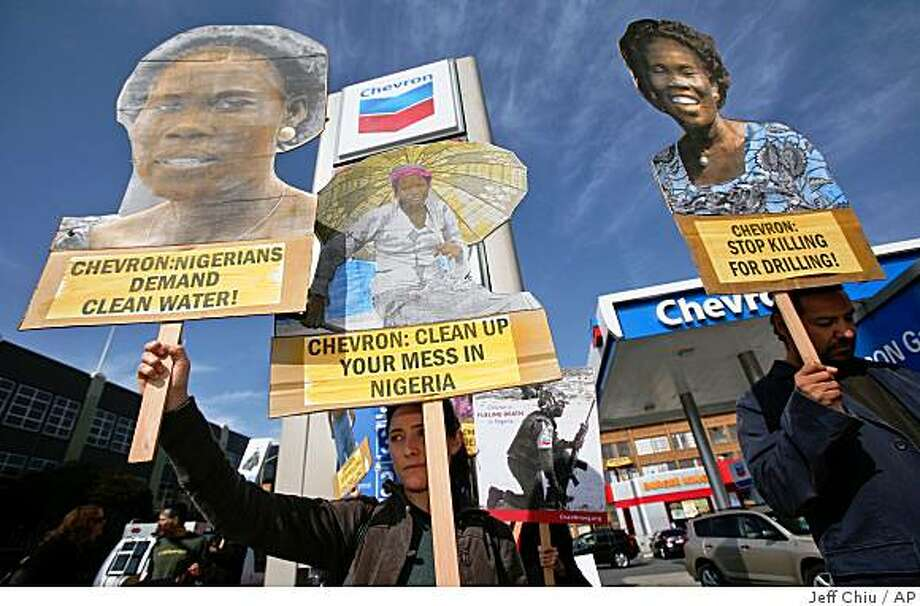 Natasha Dedrick, center, holds up signs at a protest at a Chevron gas station in San Francisco, Monday, Oct. 27, 2008. Dedrick and other activists rallied against Chevron's actions in Nigeria and to mark the opening of a human rights lawsuit against Chevron, Bowoto v. Chevron, in the U.S. Federal District Court in San Francisco. (AP Photo/Jeff Chiu) Photo: Jeff Chiu, AP
