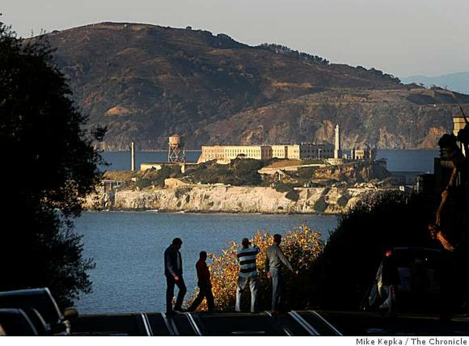 Tourists watch from the top of Lombard street as afternoon light illuminates Alcatraz Island on Friday, Nov. 21, 2008 in San Francisco, Calif. Photo: Mike Kepka, The Chronicle