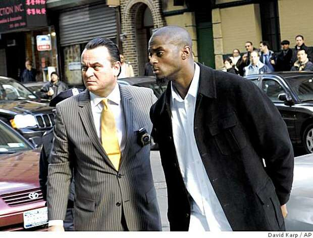 New York Giants' Plaxico Burress, right, arrives at Manhattan Supreme Court for arraignment with an unidentified man on Monday, Dec. 1, 2008, in New York. Burress accidentally shot himself at a Manhattan nightclub Friday evening and was treated at New York-Presbyterian Hospital/Weill Cornell Medical Center. He was released Saturday. (AP Photo/David Karp) Photo: David Karp, AP