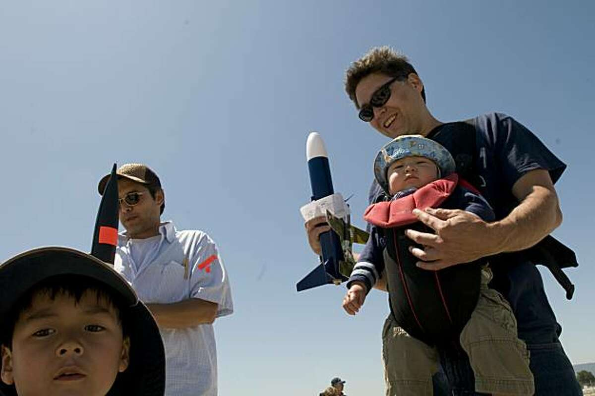 Gen Tanabe (right), 37, of Belmont, Calif., and his two sons Kane (9 mos.) and Zane (4) and friend Randy Tan, 41, of San Carlos, wait in line to have their rockets inspected prior to their launch during the Livermore Unit of the National Association of Rocketry's monthly low-power rocket launch session on Saturday, June 26, 2010 at Moffett Field/NASA Ames Research Center in Mountain View, Calif.