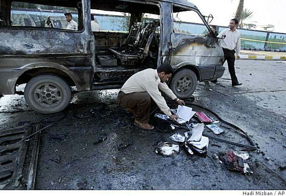 A security guard is seen looking at schoolbooks of students who were on a mini bus that was hit by a car bomb near the entrance to a police academy in Baghdad, Iraq, Monday, Dec. 1, 2008. At least 16 people were killed and 46 wounded in a nearly simultaneous double bombing near a police academy in eastern Baghdad. A suicide attacker detonated his explosives vest packed with ball-bearings at the entrance to the academy, then a car bomb exploded about 150 yards (137 meters) away, apparently aimed at those responding to the initial blast, the U.S. military said. (AP Photo/Hadi Mizban) Photo: Hadi Mizban, AP