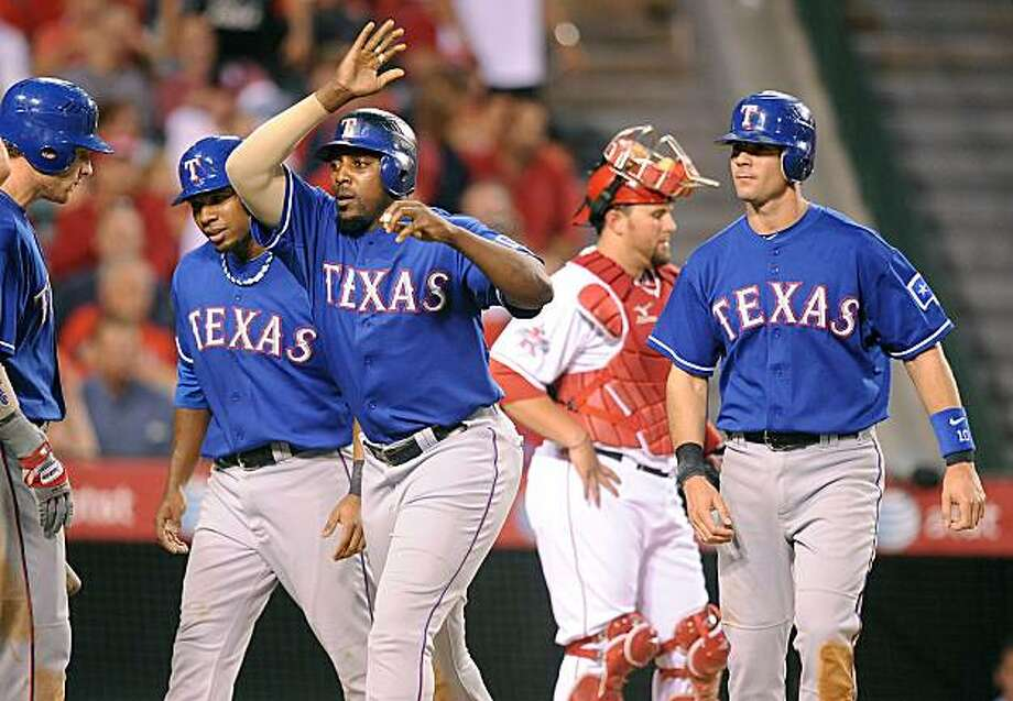 The Texas Rangers' Vladimir Guerrero, middle, is congratulated by teammates after hitting a grand slam against Los Angeles Angels pitcher Scott Kazmir in the fourth inning at Angel Stadium in Anaheim, California, on Wednesday, June 30, 2010. (Wally Skalij/Los Angeles Times/MCT) Photo: Wally Skalij, MCT