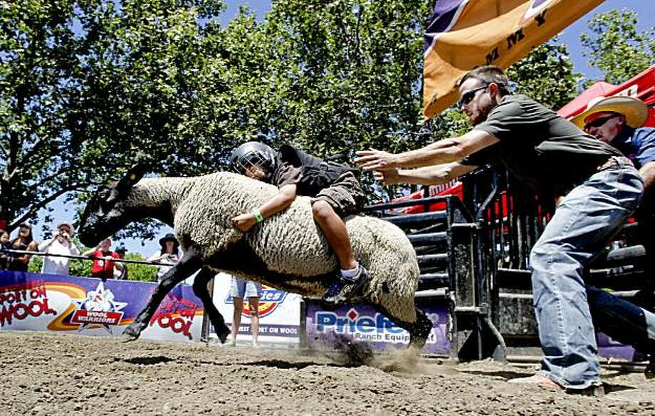 Kaleo Agustin, 4-years-old, of Danville, holds on for dear life during his shot at Mutton Bustin', during his visit to the annual Alameda County Fair  in Pleasanton, Ca. on Thursday July 1, 2010. Photo: Michael Macor, The Chronicle