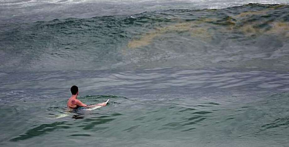 A surfer watches an oily wave approach as he waits to catch a ride in Destin, Fla., Monday, June 28, 2010.  Tourism on the Gulf coast is way off, with some hotels and condominium owners saying their business is down by 50 percent. Photo: Dave Martin, Associated Press