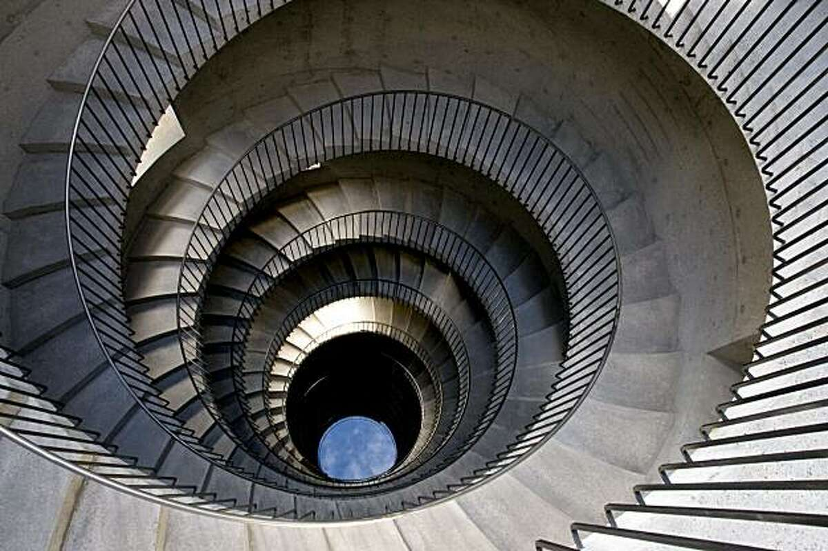 A view of the tower by artist Ann Hamilton seen from above. The open-to-the-sky cyclindrical accoutical concrete tower has double helix stairways spiraling down that never meet. One stairway is for performers and the other is for the audience. A poolat the bottom reflects the sky.
