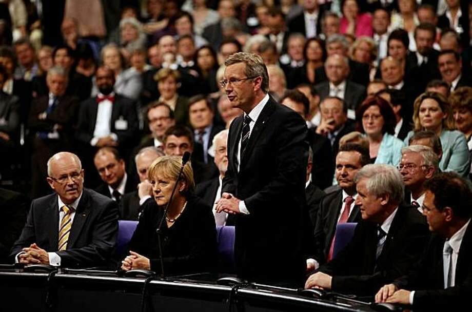 BERLIN - JUNE 30:  German presidential candidate Christian Wulff (C) accepts his mandate to become Germany's next president as German Chancellor Angela Merkel (2nd from L) looks on after Wulff won the third and final round of voting during the election ofa new German president by the Federal Assembly at the Bundestag on June 30, 2010 in Berlin, Germany. Though Wulff, the official candidate of the German Christian Democrats (CDU) and the Free Democrats (FDP), won, the fact that he needed three rounds of voting to get a majority will be seen by many as a setback for Merkel, who is also head of the CDU. Photo: Sean Gallup, Getty Images