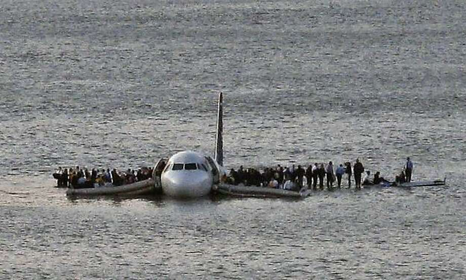 FILE - In this file photo from Jan. 15, 2009, airline passengers wait to be rescued on the wings of a US Airways Airbus 320 jetliner that safely ditched in the frigid waters of the Hudson River in New York, after a flock of Canada geese knocked out both its engines. A National Park Service official told The Associated Press on Tuesday, June 29, 2010 that for now, the government agency won't touch hundreds of birds living in a refuge at the edge of the Kennedy airport runways, even though other branches ofthe government believe that the birds pose a risk to the flying public. Photo: Steven Day, AP