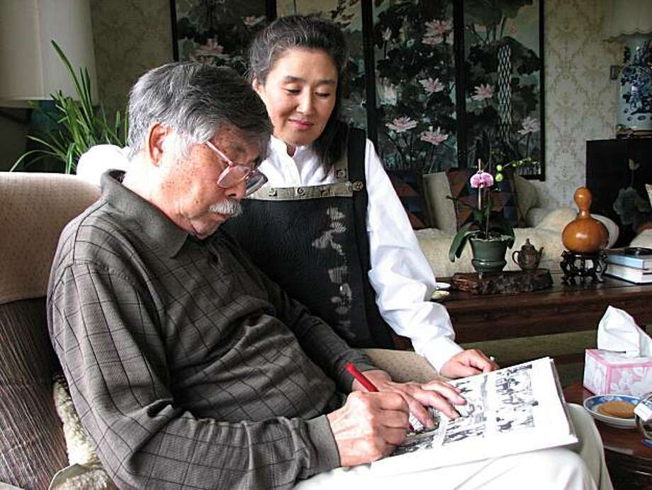 """Zu-Wu Joseph Yang, 82, uses a red pen to add more of his story to the ink drawings depicting his life in his daughter Belle Yang's book, """"Forget Sorrow."""" Photo: Meredith May"""