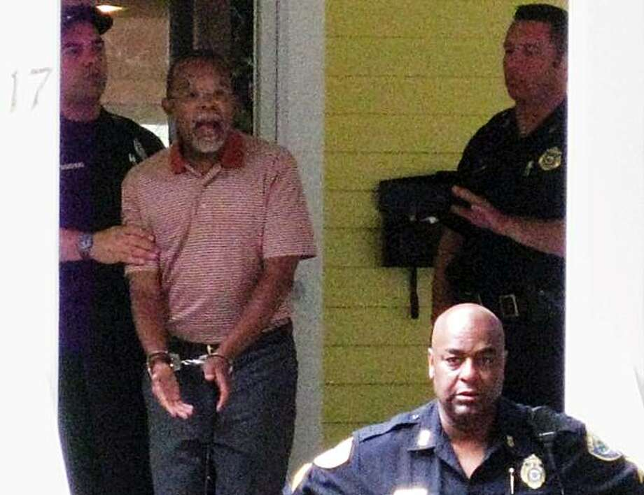 FILE - In this file photo taken by a neighbor July 16, 2009, Henry Louis Gates Jr. center, the director of Harvard University's W.E.B. DuBois Institute for African and African American Research, is arrested at his home in Cambridge, Mass. Police just outside Boston are expected to release results of an independent review of last year's arrest of black Harvard University scholar Henry Louis Gates Jr. by a white sergeant Wednesday, June 30, 2010. Photo: B. Carter, AP