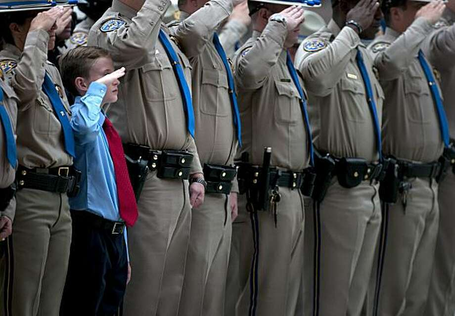 George Clare, 11, joins his mother, CHP officer Laura Clare in a salute along with California Highway Patrol (CHP) officers at the funeral of CHP Officer Philip Ortiz at the Cathedral of Our Lady of the Angels on Wednesday, June 30, 2010, in Los Angeles.Ortiz, one of five CHP officers killed on the job since May 2010, was fatally injured on June 9 when he was hit by a car while writing a ticket on the 405 Freeway. Photo: Adam Lau, AP