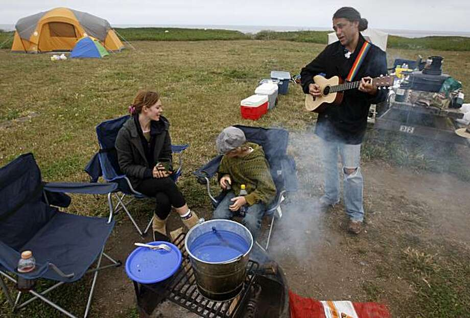 Tony Suraci serenades Lana Skinner and his son Joseph while camping at Half Moon Bay State Beach in Half Moon Bay, Calif., on Tuesday, June 29, 2010. Suraci, Skinner and his two sons left their Riverside County home for a 12-day camping trip up and down the state. Suraci originally hoped to travel to South Dakota this year but high gas prices convinced him to stay within California. Photo: Paul Chinn, The Chronicle