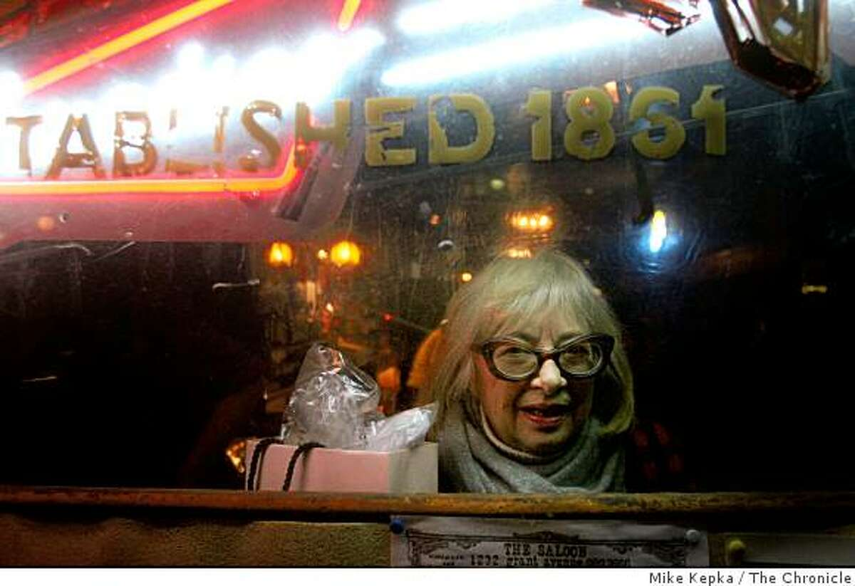 """In North Beach, Ruby MacKenzie looks out of a dimly lit window at """"The Saloon"""", San Francisco's oldest bar, on Friday, Nov. 21, 2008 in San Francisco, Calif."""