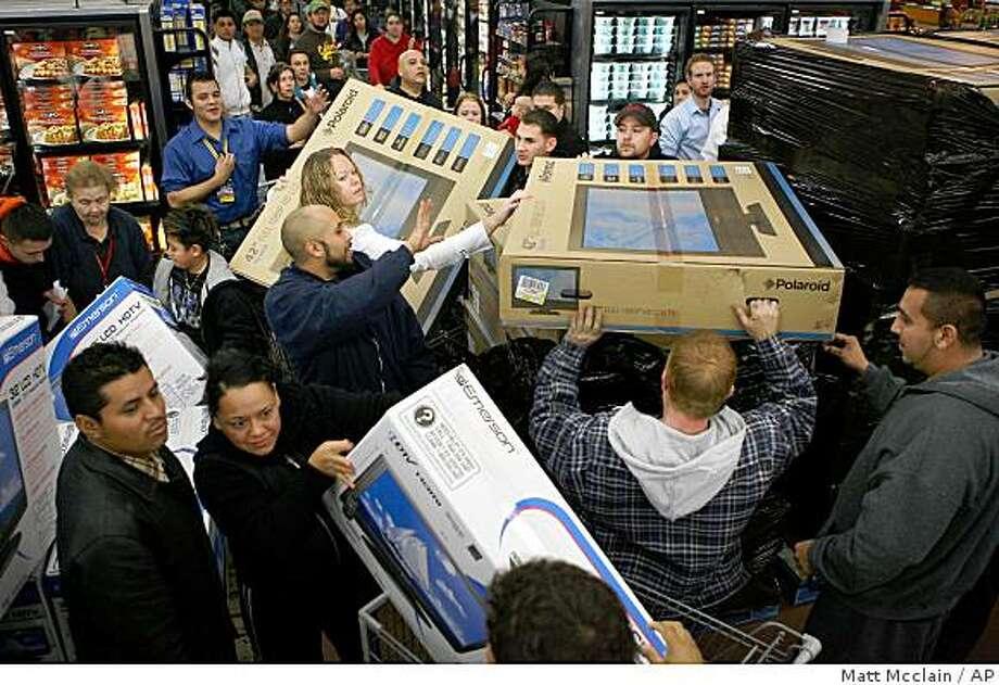 Television sets move off a display at Wal-Mart in Lakewood, Colo. on Friday, Nov. 28, 2008. (AP Photo/Rocky Mountain News, Matt Mcclain) ** DENVER POST OUT, MAGS OUT, NO SALES,  MANDATORY CREDIT ** Photo: Matt Mcclain, AP