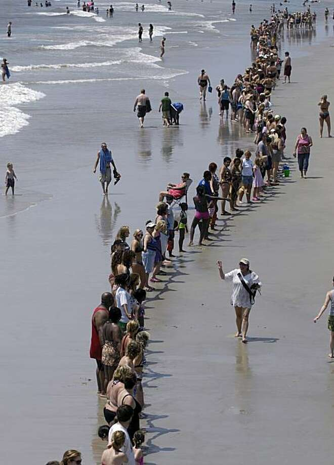 Hundreds of people join hands while taking part in the Hands Across the Sand movement Saturday, June, 26, 2010 in Tybee Island, Ga. One of the national movement's goal is to oppose offshore oil drilling and champion clean and renewable energy. Photo: Stephen Morton, AP