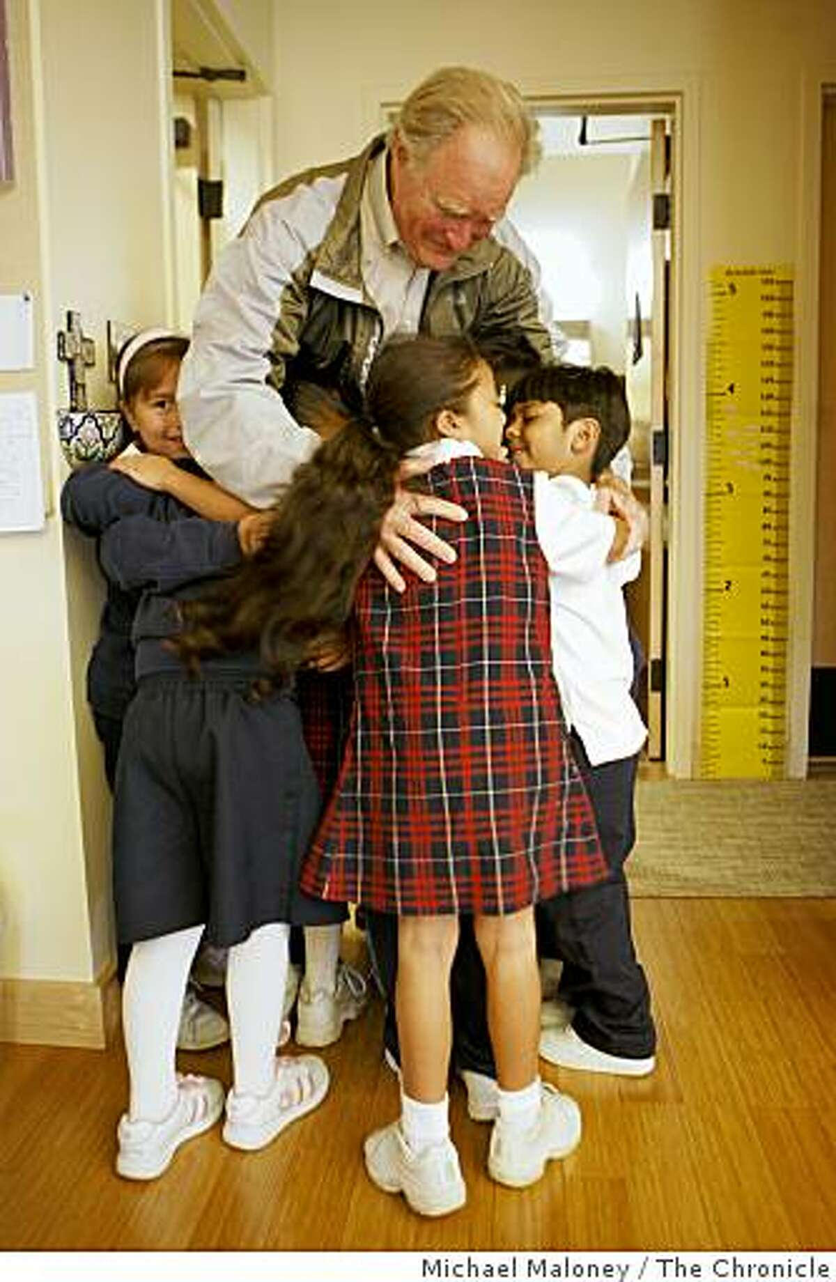 """Philanthropist Bill Somerville gets a hug from the Holy Family School students at the St. Francis Center in Redwood City, Calif., on November 19, 2008 - one of the many organizations he has helped out. The first graders all ran to him yelling """"Mr. Bill!"""" on his visit to the class."""