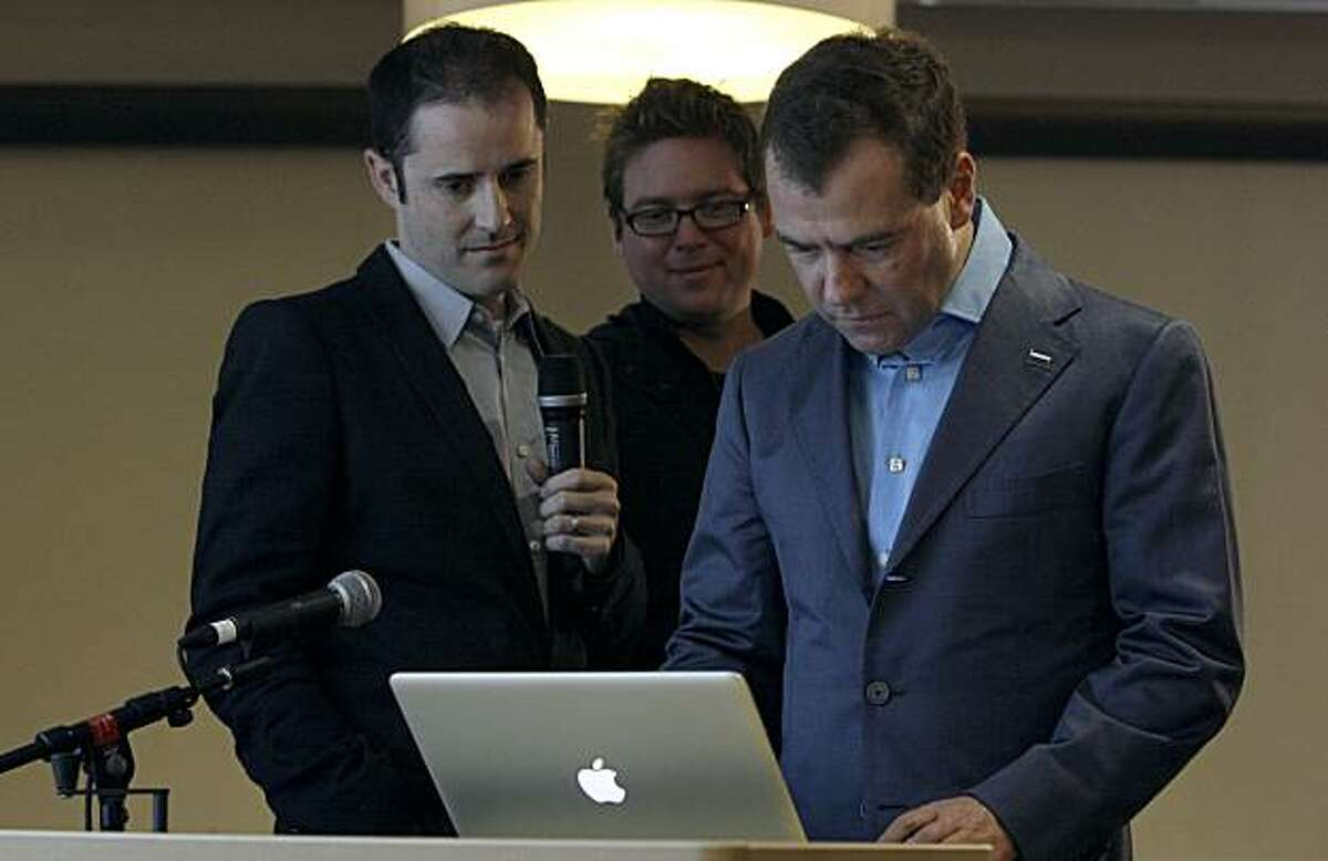 President of Russia Dmitry Medvedev, right, writes a Twitter message as Twitter co-founders Evan Williams, left, and Biz Stone watch at the Twitter office in San Francisco, Wednesday, June 23, 2010.