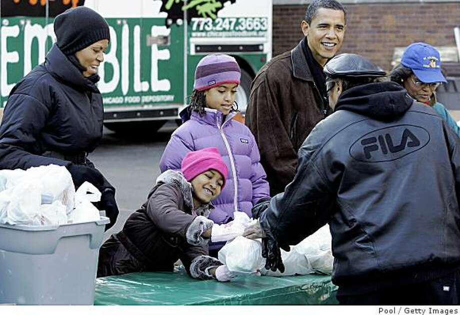 CHICAGO - NOVEMBER 26:  President-elect Barack Obama (R), wife Michelle (L) and daughters Sasha (2nd L) and Malia, pass out food at St. Columbanus Parrish and School November 26, 2008, in Chicago, Illinois. Obama earlier intruduced Paul Volckeras the chair of his Economic Recovery Advisory Board.  (Photo  by Frank Polich-Pool/Getty Images) Photo: Pool, Getty Images