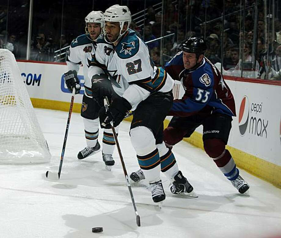San Jose Sharks center Manny Malhotra, front, clears the puck with Colorado Avalanche left winger Cody McLeod, center, in pursuit as Sharks defenseman Kent Huskins trails the play in the third period of the Sharks' 5-2 victory in Game 6 of the teams' first-round NHL Western Conference playoff series in Denver on Saturday, April 24, 2010. With the win, the Sharks advance to the next round of the playoffs. Photo: David Zalubowski, AP