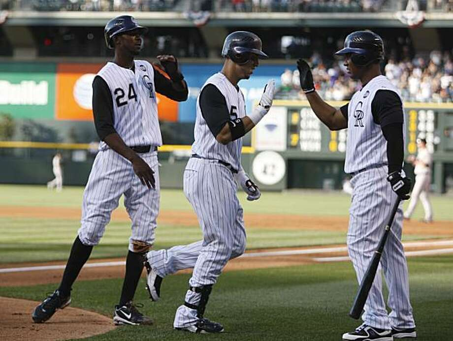 Colorado Rockies' Carlos Gonzalez, center, is congratulated by teammates Dexter Fowler, left, and Melvin Mora after Gonzalez hit a two-run home run against the San Francisco Giants in the first inning of a baseball game in Denver on Thursday, July 1, 2010. Photo: David Zalubowski, AP