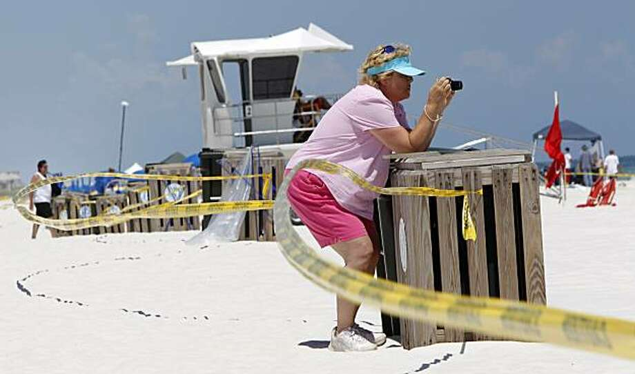 Mary Ann Sadler of Gulf Breeze, Fla., leans across the police tape to take photos of oil cleanup efforts at Pensacola Beach, Fla., Thursday, June 24, 2010. Pensacola Beach officials have closed the public beaches to swimmers. Oil from the Deepwater Horizon disaster continues to wash ashore along the Alabama and Florida coasts. Photo: Dave Martin, AP
