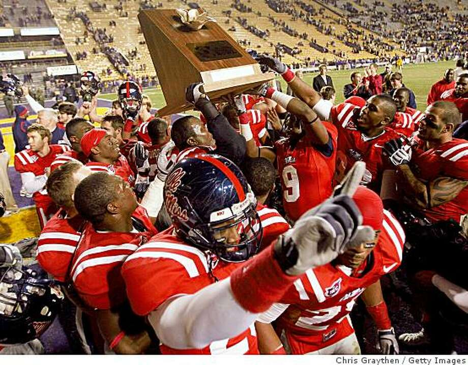 """BATON ROUGE, LA - NOVEMBER 22:  Members of the Ole Miss Rebels celebrate with the """"Magnoila Bowl"""" trophy after defeating the Louisiana State University Tigers 31-13 on November 22, 2008 at Tiger Stadium in Baton Rouge, Louisiana.  (Photo by Chris Graythen/Getty Images) Photo: Chris Graythen, Getty Images"""