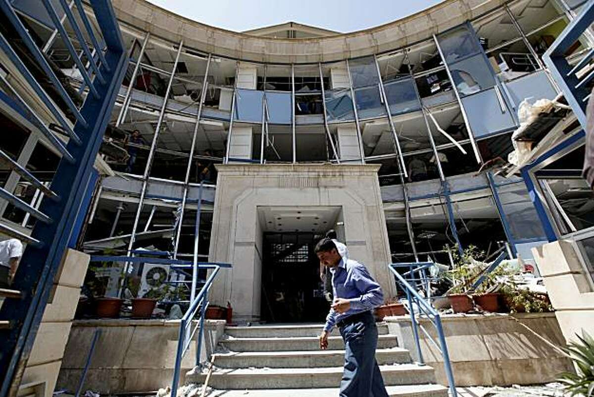 FILE - In this Monday, June 21, 2010 file photo, an Iraqi man passes near a bank that was severely damaged in a car bomb attack in Baghdad, Iraq. An al-Qaida front group gloated over its ease in penetrating security around a state-run investment bank in astatement Wednesday claiming responsibility for a Baghdad bombing this week that killed several people and wounded scores more.