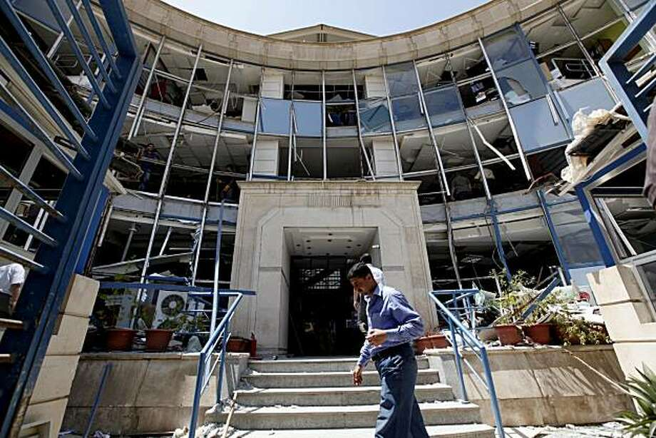 FILE - In this Monday, June 21, 2010 file photo, an Iraqi man passes near a bank that was severely damaged in a car bomb attack in Baghdad, Iraq. An al-Qaida front group gloated over its ease in penetrating security around a state-run investment bank in astatement Wednesday claiming responsibility for a Baghdad bombing this week that killed several people and wounded scores more. Photo: Hadi Mizban, AP