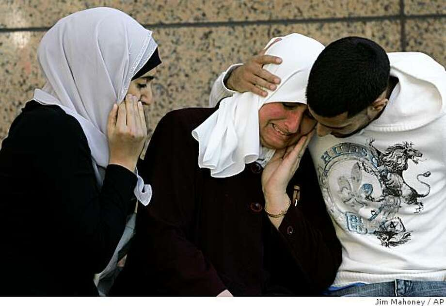 Zolfa Elaydi cries with her daughter Fidaa Elaydi, left, and Jihad Elaydi in reaction to a verdict of guilty on all counts for the defendants in the Holy Land Foundation trial on Monday, Nov. 24, 2008 at the Earle Cabell Federal Building in Dallas, Texas. The jury determined that the Holy Land Foundation and five men who worked with the Muslim charity were guilty of three dozen counts related to the illegal funneling of money to the Palestinian terrorist group Hamas. Ghassan Elashi, Holy Land's former chairman, and Shukri Abu-Baker, the chief executive, were convicted of a combined 69 counts, including supporting a specially designated terrorist, money laundering and tax fraud.  (AP Photo/Jim Mahoney/The Dallas Morning News)  ** NO SALES, MAGS OUT, TV OUT, INTERNET USE BY AP MEMBERS ONLY ** Photo: Jim Mahoney, AP