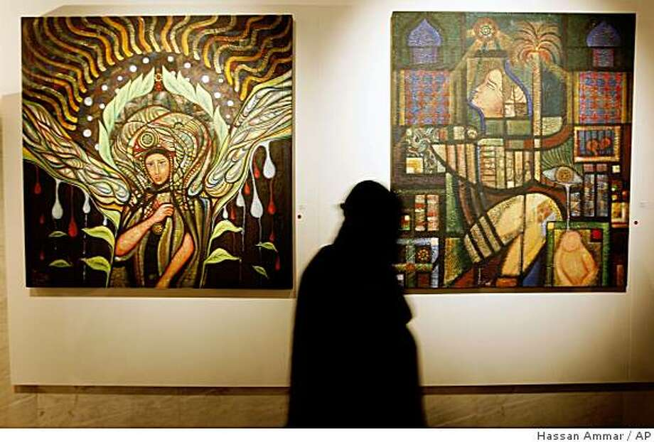 A Saudi woman looks at artwork during the opening of art exhibition featuring the work of seven  Saudi female artists at the French Embassy in Riyadh, Saudi Arabia, Wednesday, Nov. 26, 2008. (AP Photo/Hassan Ammar) Photo: Hassan Ammar, AP