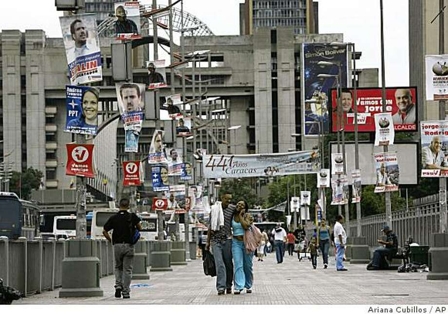 Pedestrians along a street covered by campaign signs in Caracas, Saturday, Nov. 22, 2008.  Venezuela will hold regional elections Sunday.  (AP Photo/Ariana Cubillos) Photo: Ariana Cubillos, AP