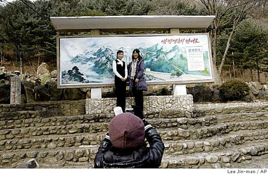 A South Korean tourist, right, poses with North Korean woman, left, for a photo during a tour to North Korea city Kaesong, North Korea, Saturday, Nov. 22, 2008. State-run North Korean media say its military has informed the South it will follow through with a plan to restrict overland passage through their heavily armed border starting Dec. 1.  The report says the border shutdown will mean a total suspension of tourism to the North Korean city of Kaesong.  (AP Photo/ Lee Jin-man) Photo: Lee Jin-man, AP