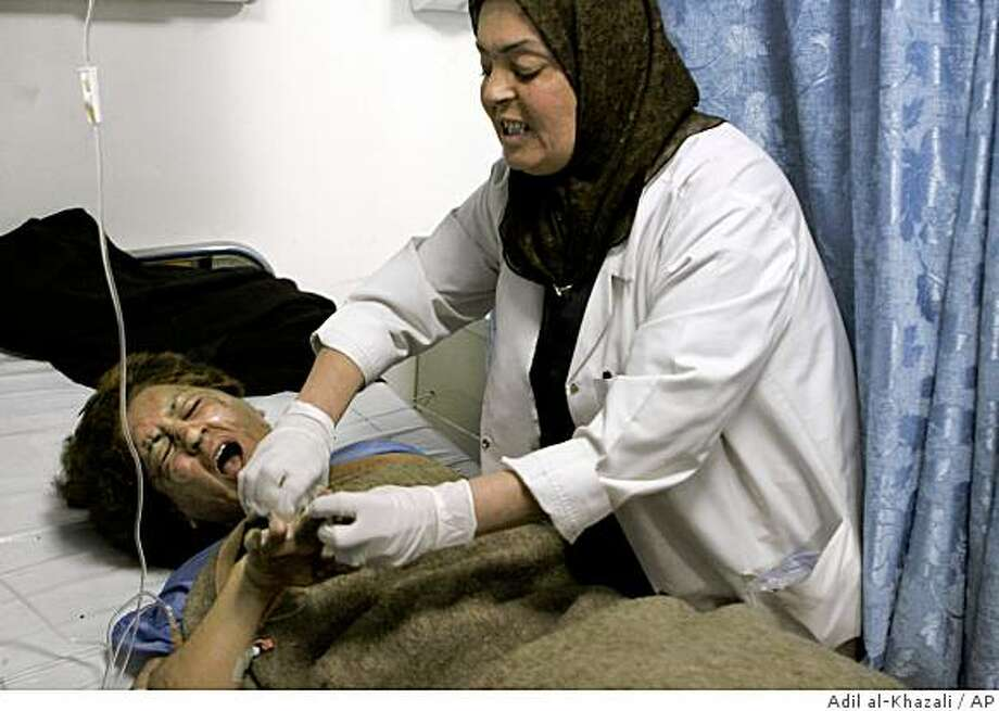 An Iraqi woman cries out in pain as she is treated for burns after a bus bombing in Baghdad, Iraq, on Monday, Nov. 24, 2008.  A female suicide bomber blew herself up near an entrance to the U.S.-protected Green Zone and a bomb tore through a bus carrying Iraqi government employees in separate attacks on Monday, killing at least 18 people, Iraqi officials said. (AP Photo/Adil al-Khazali) Photo: Adil Al-Khazali, AP