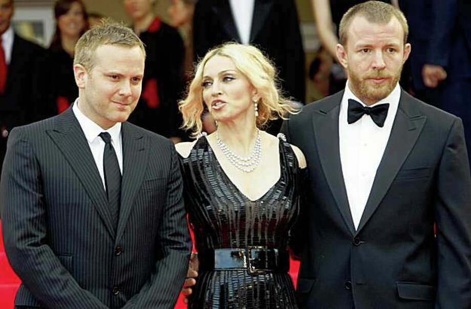 Singer Madonna (C) stands between director Nathan Rissman (L) and her director husband Guy Ritchie on the red carpet at the 61st Cannes Film Festival May 21, 2008. Photo: Jean-Paul Pelissier, Reuters