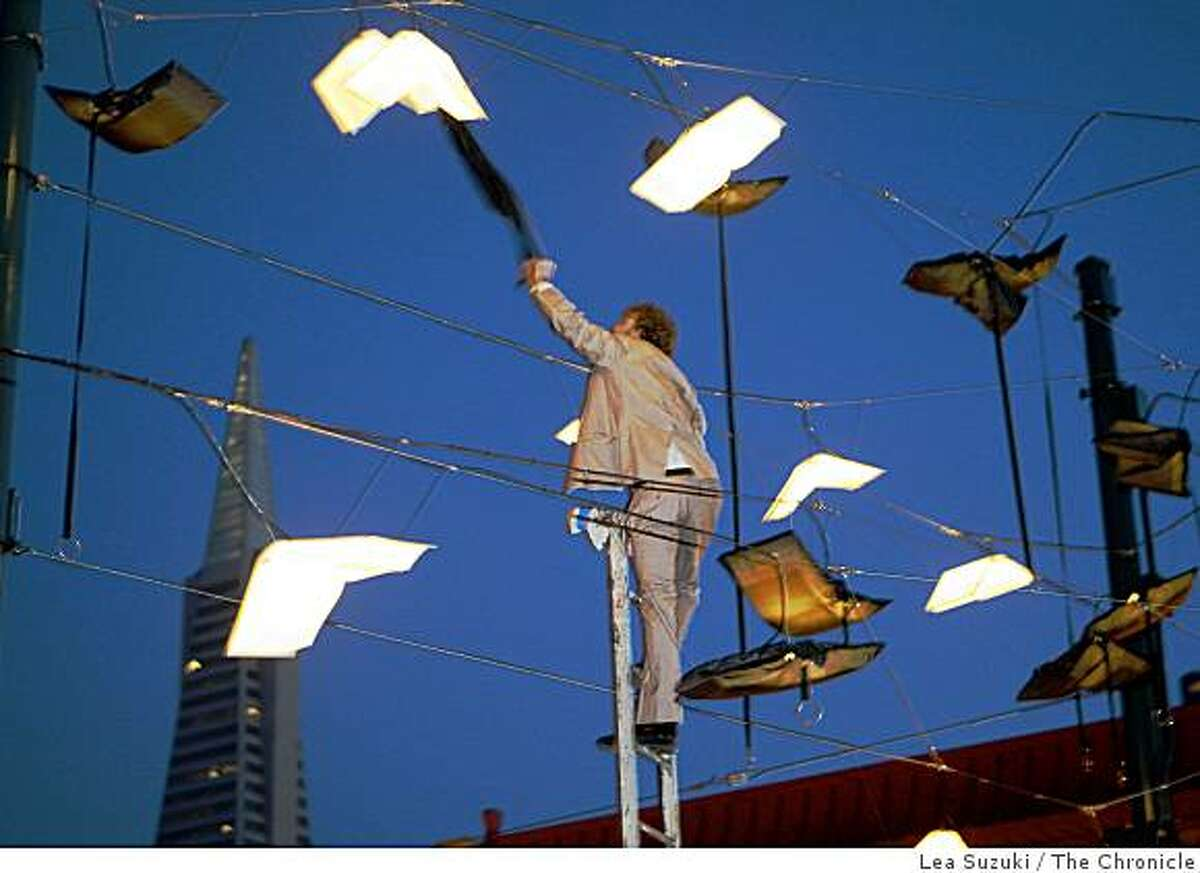"""Brian Goggin attempts to remove a cloth light cover that became stuck on one of the lights during the unveiling of """"Language of the Birds"""" in San Francisco, Calif. on Sunday, November 23, 2008. """"Language of the Birds"""" a permanent site-specific sculpture the evokes books taking flight is unveiled on the corner of Broadway and Columbus Streets. The artists are Brian Goggin and Dorka Keehn."""