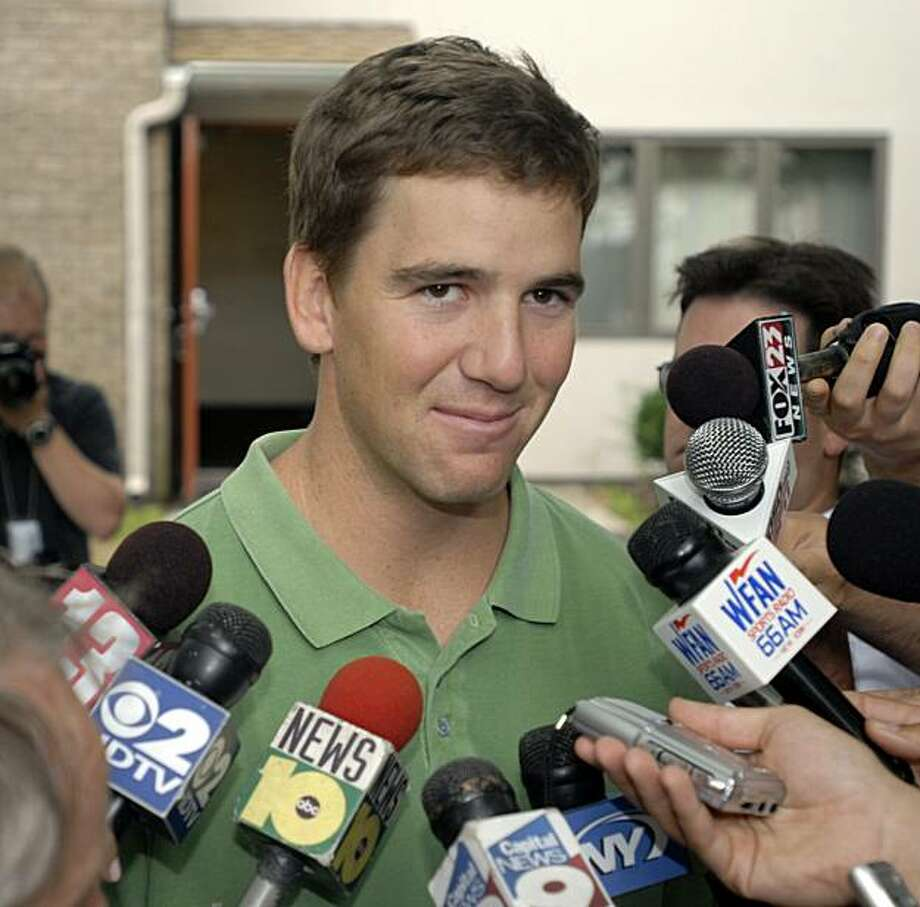 FILE -- This is an Aug. 2, 2009, file photo showing Eli Manning speaking with reporters after arriving for the start of New York Giants NFL football training camp in Albany, N.Y. Eli Manning has agreed to a new six-year, $97 million contract extension with the New York Giants that will make him the highest paid player in the NFL with an average salary of roughly $15.3 million. A person close to the talks who asked not to be identified because the deal was not signed says Manning is guaranteed $35 million under the deal which will keep him with the Giants through the 2015 season. (AP Photo/Tim Roske, File) Photo: Tim Roske, AP