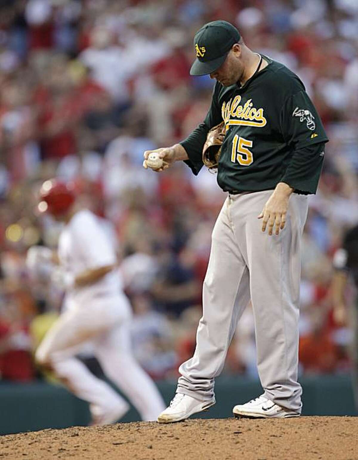 Oakland Athletics starting pitcher Ben Sheets (15) kicks the mound as St. Louis Cardinals' Matt Holliday, background, circles the bases after hitting a two-run home run in the seventh inning of a baseball game, Saturday, June 19, 2010, in St. Louis.