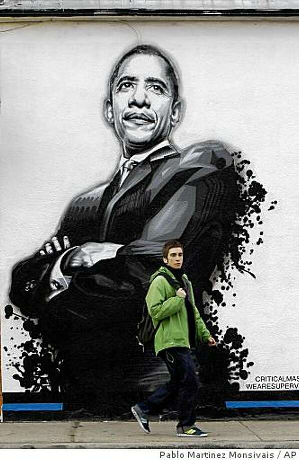 Jordan Warburton, 25, from Manchester, England, walks past a mural portrait of President-elect Barack Obama that is painted on the side of a restaurant on North Halsted St., in Chicago, Sunday, Nov. 23, 2008. (AP Photo/Pablo Martinez Monsivais) Photo: Pablo Martinez Monsivais, AP