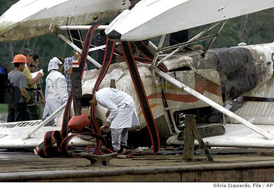 """**FILE** Authorities inspect the wreckage of a Cessna plane after it was  raised from the Amazon River in Huanta, in the Peruvian state of Iquitos, on April 26, 2001. A Peruvian air force jet which mistook it for a drug flight gunned it from the skies Friday. American missionary Veronica """"Roni"""" Bowers and her 7-month-old daughter Charity were killed in the April 20, 2001 attack. A classified CIA report on the 2001 shoot down of a small plane carrying American missionaries by the Peruvian air force suggests U.S. officials may have misled Congress and withheld information from the Justice Department.   (AP Photo/Silvia izquierdo, file) Photo: Silvia Izquierdo, File, AP"""