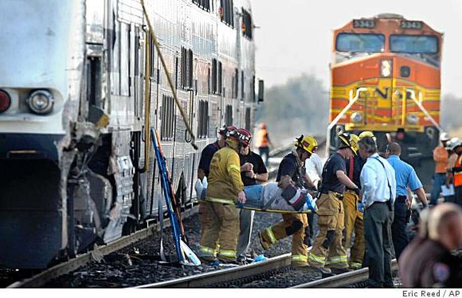 Firefighters remove a passenger on a stretcher from a Metrolink train after a collision with a BNSF freight train in Rialto, Calif., Thursday, Nov. 20, 2008. The accident comes nine weeks after the deadliest crash in Metrolink history. (AP Photo/The Sun, Eric Reed) ** LA TIMES OUT, VENTURA COUNTY STAR OUT, RIVERSIDE PRESS-ENTERPRISE OUT, THE VICTOR VALLEY DAILY PRESS OUT ** Photo: Eric Reed, AP