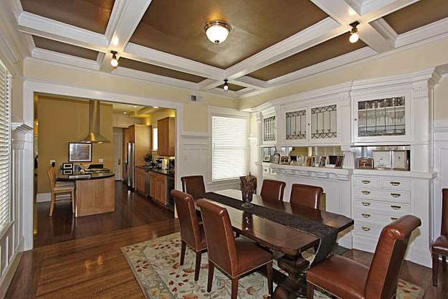 The formal dining room, which includes original wainscoting, high box beam ceilings and built-ins, opens to the modern kitchen. Photo: John Arbuckle
