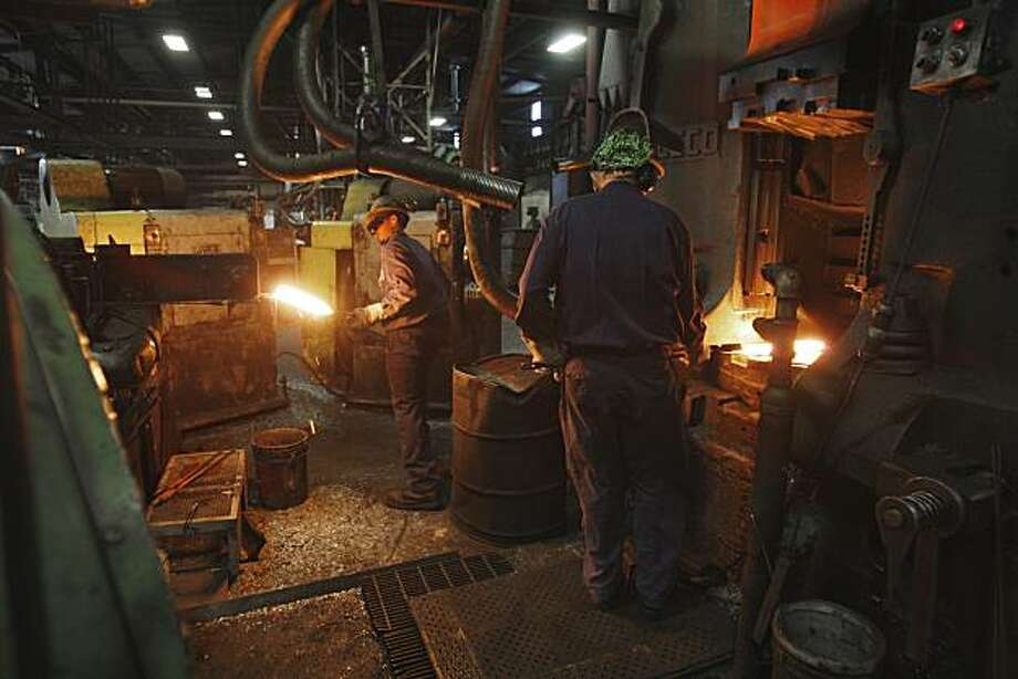 Trenton Forging workers stamp steel car components in Trenton, Mich., Wednesday, May 12, 2010.  Using orange-hot metal that's been forged into everything from car components and hand tools to machine gun parts, the manufacturer is working to turn wasted heat into nurturing warmth for a year-round, rooftop greenhouse. Photo: Carlos Osorio, AP