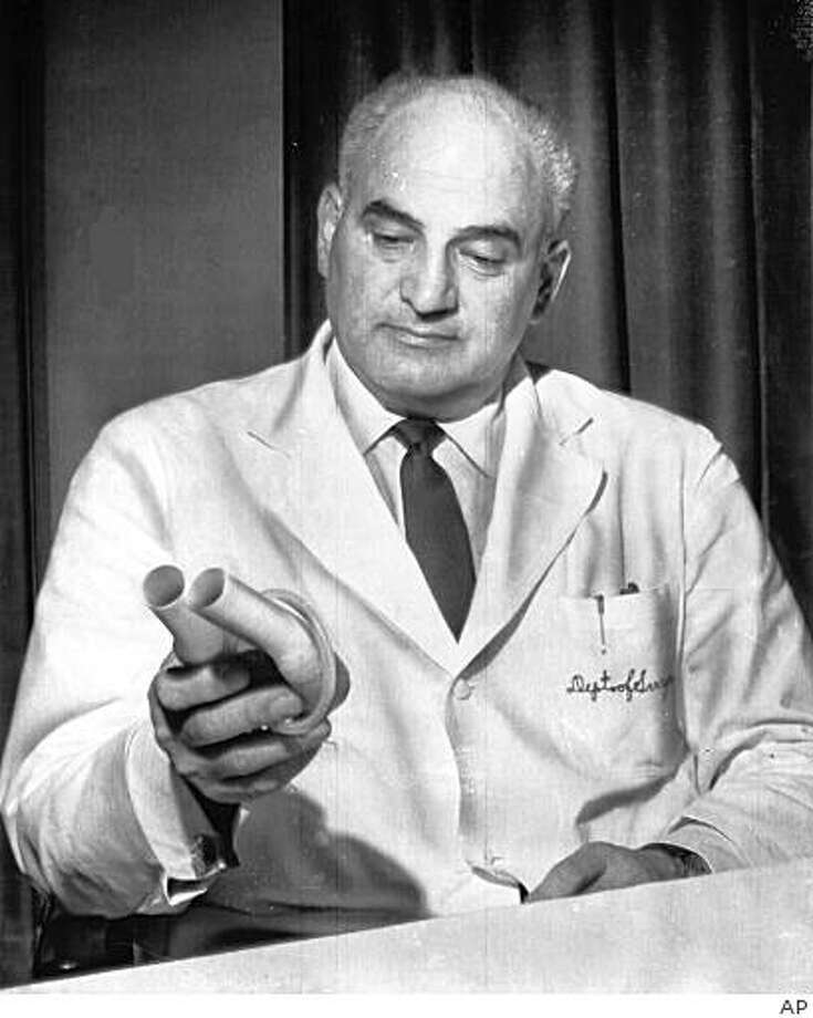 ** FILE ** In this  May 23, 1966 file photo, American heart specialist Dr. Adrian Kantrowitz displays a mechanical auxillary heart, like the one he implanted in Mrs. Louise Ceraso, in a New York hospital, six days previous, during a news conference in New York. Dr. Kantrowitz, who performed the first human heart transplant in the United States in 1967 and pioneered development of mechanical devices to prolong the life of patients with heart failure, died in Ann Arbor, Mich., Friday, Nov. 14, 2008. He was 90. (AP Photo, File) Photo: AP