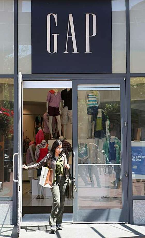 In this photo taken Tuesday, May 19, 2009, a woman walks out of a Gap store in San Francisco. Gap Inc. on Thursday, May 21 reported that its first-quarter profit fell almost 14 percent as the clothing chain faced sluggish consumer demand during the recession, but the results narrowly beat Wall Street estimates. (AP Photo/Jeff Chiu) Photo: Jeff Chiu, AP