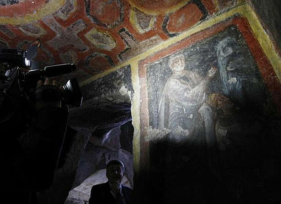 A cameraman films a painting discovered with the earliest known icons of the Apostles Peter and Paul in a catacomb located under a modern office building in a residential neighborhood of Rome, Tuesday, June, 22, 2010. Restorers said Tuesday they had unearthed the 4th-century images using a new laser technique that allowed them to burn off centuries of white calcium deposits without damaging the dark colors of the original paintings underneath. The paintings adorn what is believed to be the tomb of a Romannoblewoman and represent some of the earliest evidence of devotion to the apostles in early Christianity. Photo: Pier Paolo Cito, AP