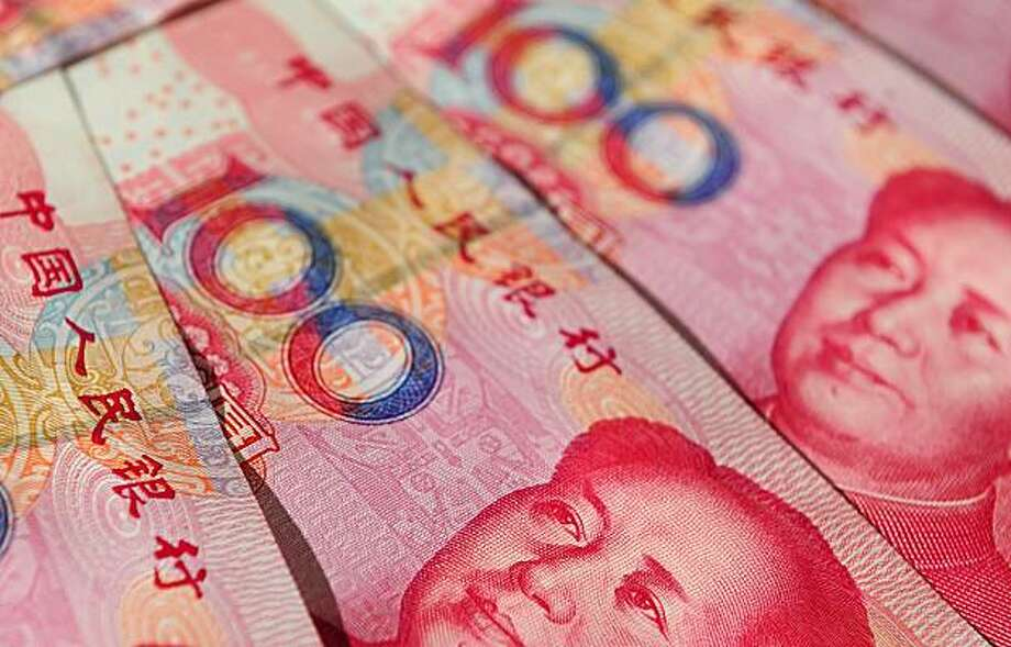 Former Chinese Communist Party leader Mao Zedong's image is seen in an illustration display of Chinese currency 100 Yuan (or Renmibi) notes in Beijing on June 21, 2010. The USD lost ground in Asia after China's yuan exchange rate hit its highest level against the USD in five years following a weekend announcement of greater flexibility, analysts said. Photo: Frederic J. Brown, AFP/Getty Images