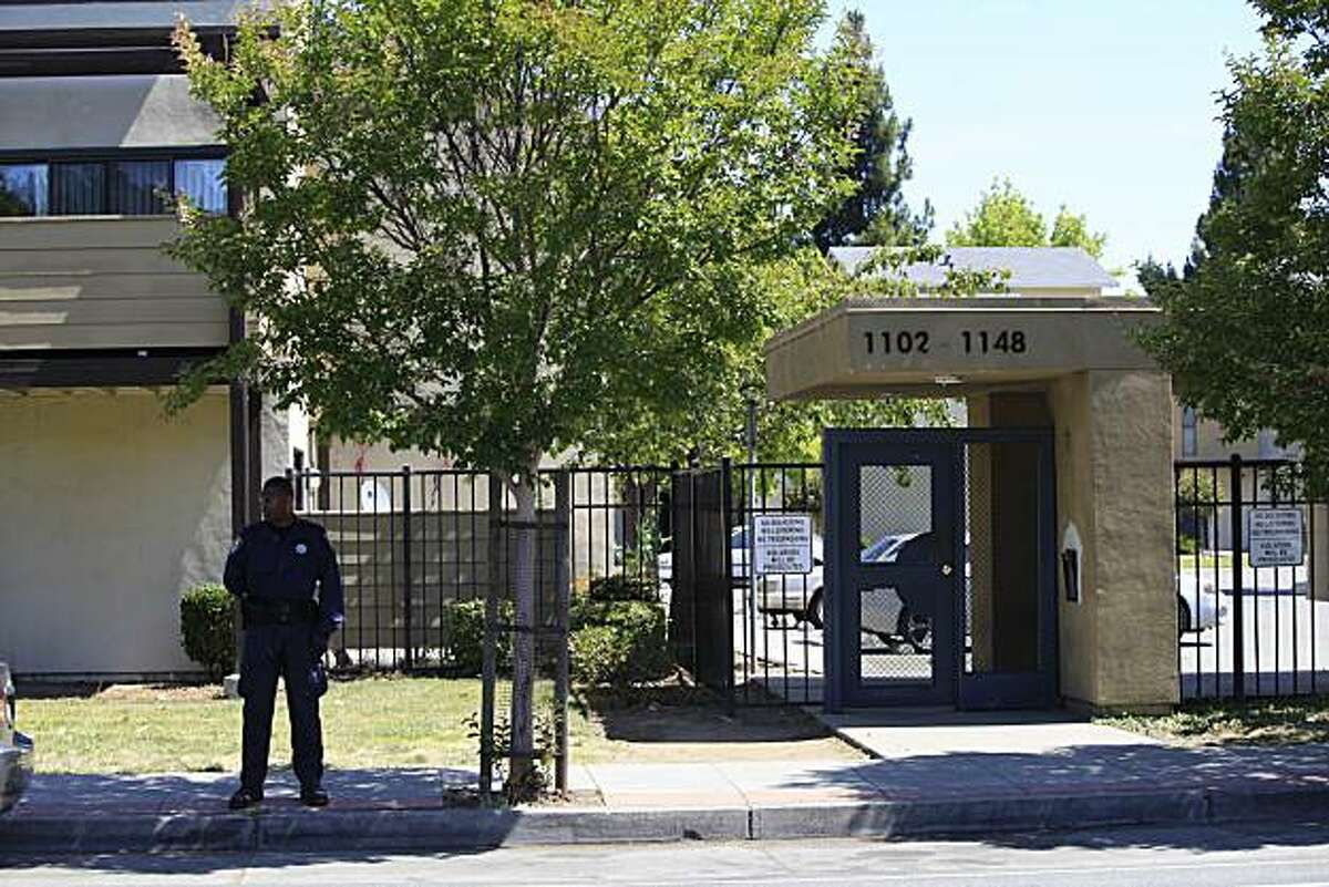 In this file photo, a security guard stands in front of the the Acorn housing complex on the 1100 block of Eighth Street in Oakland. FBI SWAT team and Oakland police converged on the housing complex making