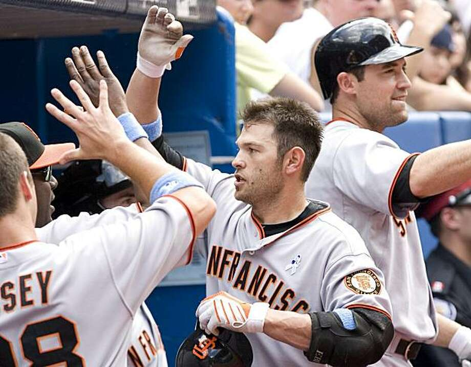 San Francisco Giants' Freddie Sanchez, center, is congratulated by teammates in the dugout after hitting a three-run home run off Toronto Blue Jays pitcher  Brian Tallet during sixth-inning interleague baseball game action in Toronto on Sunday, June 20  2010. Photo: Chris Young, AP